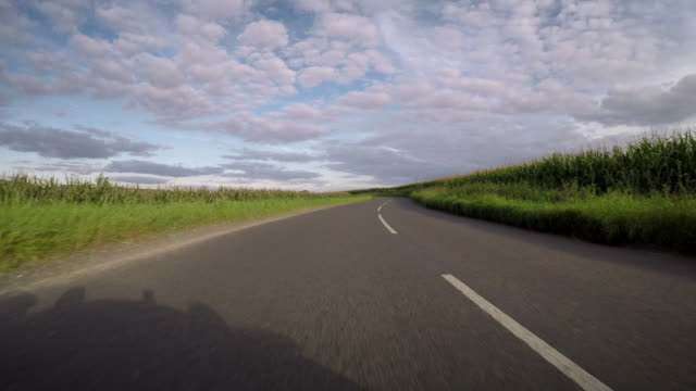 vidéos et rushes de pov from a car in open countryside negotiates a number of bends on the road the shadow of a classic caterham 7 sports car is cast on the road - effet de perspective