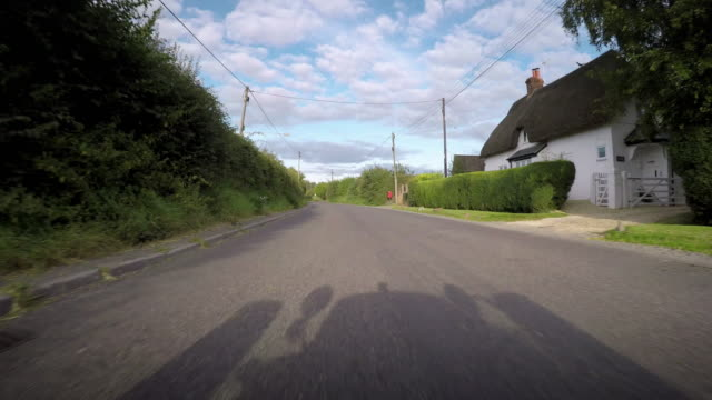 vídeos y material grabado en eventos de stock de pov from a car passing houses and cottages as it drives through a small country village the shadow of a classic caterham 7 sports car is cast on the road - poste telegráfico