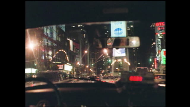"""from a moving car driving toward times square at night, lots of neon signs and billboards along the street """"smooth character"""" """"united artists""""... - billboard stock videos & royalty-free footage"""