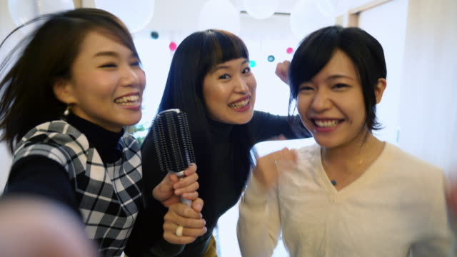 pov from a phone as three young japanese women sing karaoke at home - three people stock videos & royalty-free footage