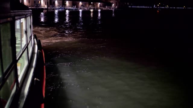 pov from a vaporetto boat in venice, italy at night. city of romance, floating in the venetian canals with the typical venetian sights. - barca a motore video stock e b–roll
