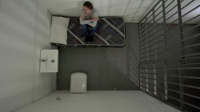 vídeos de stock, filmes e b-roll de 4k de cima: reclusa na cela sat na cama - batendo com a cabeça na parede