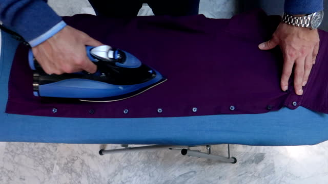 from above man ironing shirt - stock video - iron appliance stock videos and b-roll footage