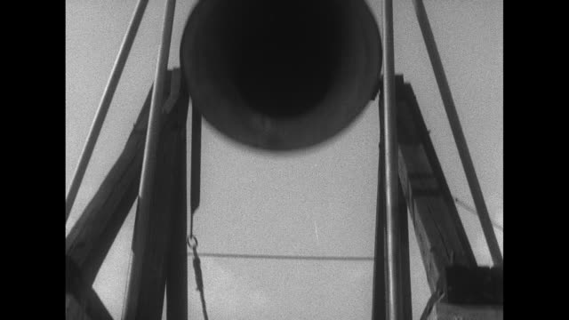 motorcade of buses pulls into town drives through crowds of cheering handkerchief waving people / man pulls rope to ring suspended bell tilt up to... - 1955 stock-videos und b-roll-filmmaterial
