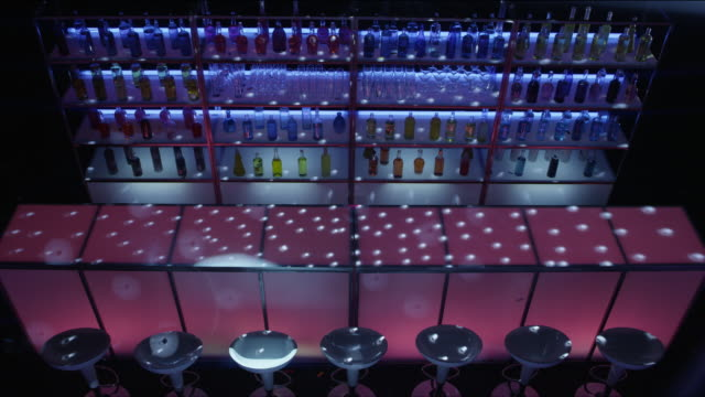 ws from above of nightclub bar and drinks with flashing lights - bar stock-videos und b-roll-filmmaterial