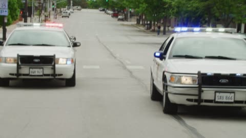 pov from action shot from the rear of a vehicle racing down the street pursued by two police cars with flashing lights; all cars squeal to an abrupt stop. (license plates are not real – plates are props.) - pursuit concept stock videos & royalty-free footage
