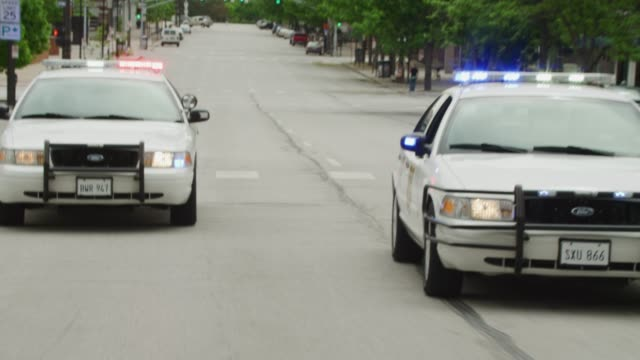pov from action shot from the rear of a vehicle racing down the street pursued by two police cars with flashing lights; all cars squeal to an abrupt stop. (license plates are not real – plates are props.) - police car stock videos & royalty-free footage