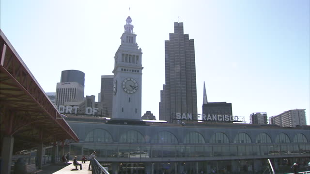 from angled ws partial san fran ferry building clock tower to ha ws various unidentifiable people on pier walking boarding docked ferry boat ca san... - san francisco ferry building stock videos & royalty-free footage