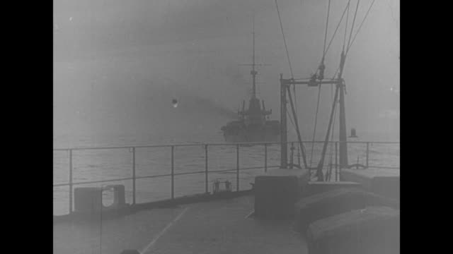 from another ship: a line of battleships moves away / from ship deck of ship in front / large cannons with the ships in the distance; a closer view... - ww1 battle stock videos & royalty-free footage