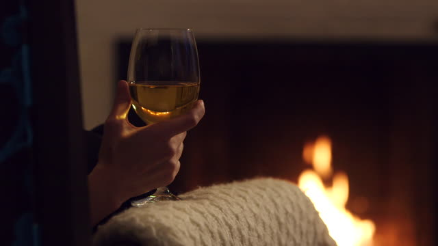 pan from armchair to glass of white wine and fireplace - wine glass stock videos and b-roll footage
