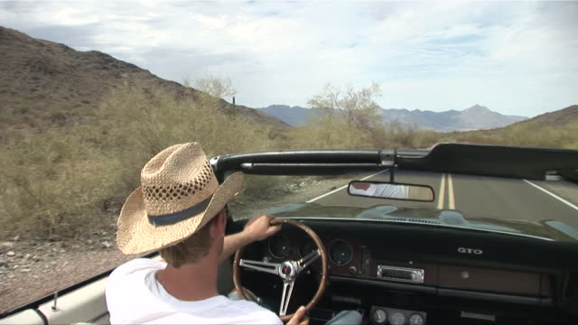 passenger pov from back seat of convertible as man in straw hat drives down desert road/ scottsdale, arizona - see other clips from this shoot 1050 stock videos and b-roll footage