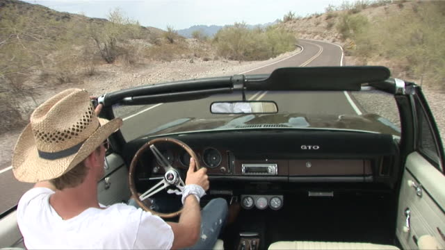 passenger pov from back seat of convertible as man in straw hat drives down desert road/ scottsdale, arizona - straw hat stock videos & royalty-free footage
