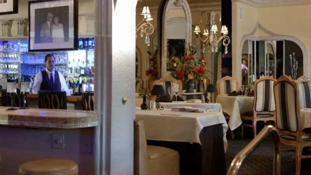 TS from bar area to empty dining room in upscale restaurant furnished French traditional