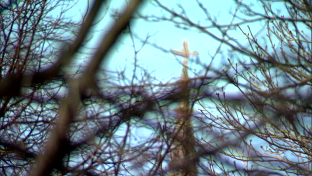from bare tree branches fg to simple gold cross on top of church steeple bg, clear blue sky. christian symbol, christianity, iconic, religion,... - steeple stock videos & royalty-free footage