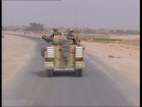 from basra pool iraq near basra ext track forward thru outskirts of town on moving tank track along behind british tank as along road into town... - basra video stock e b–roll