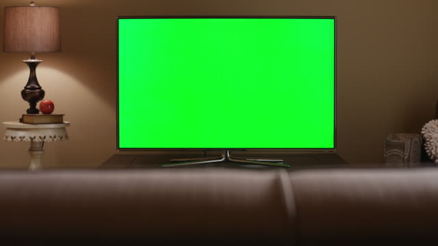 from behind a living room sofa, camera pedestals to reveal a  large screen tv which is green screen for content replacement. - television set stock videos & royalty-free footage