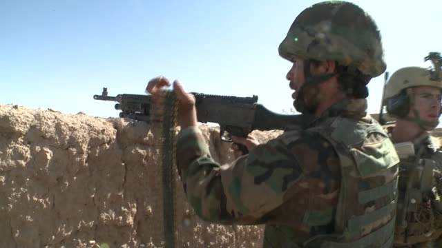 from behind backs of us army soldiers aiming their guns during war in afghanistan - war or terrorism or military点の映像素材/bロール