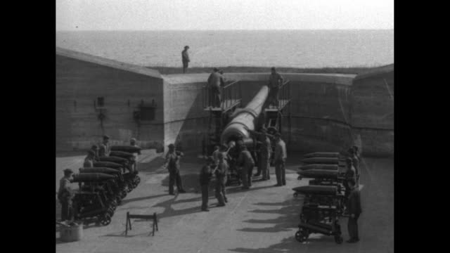 gun below parapet of concrete wall soldiers stand by rows of shells two push shell into back of gun others with long pole step forward and push shell... - artiglieria video stock e b–roll