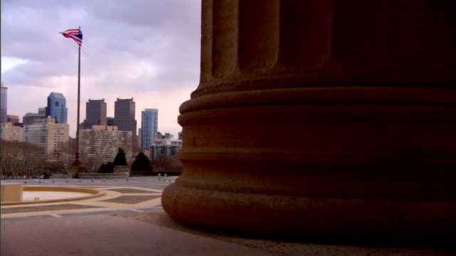 from behind pillar on front facade of philadelphia museum of art revealing skyline of center city w/ large skyscraper buildings 2 american flags... - center city philadelphia stock videos and b-roll footage