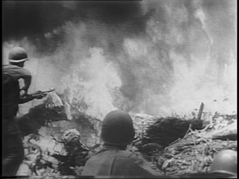 from behind, us soldier with flamethrower clears brush in jungle / american soldiers and trucks advance on dirt road through jungle, picking up... - stillahavsöarna bildbanksvideor och videomaterial från bakom kulisserna