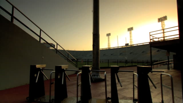 vídeos de stock e filmes b-roll de from behind wall toward & past turnstiles & column, empty stadium & field, blue/orange sky w/ white sunlight. no people, college, professional,... - torniquete divisa