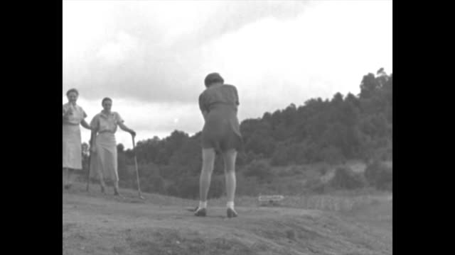 ms from behind woman in shorts drives golf ball two other women in bkgd with golf clubs / note exact day not known - shorts stock-videos und b-roll-filmmaterial
