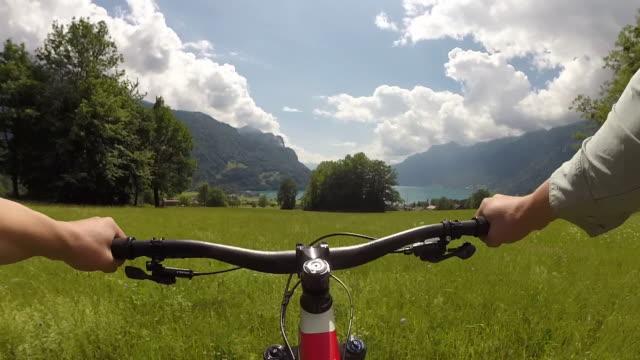 vídeos de stock e filmes b-roll de pov from bicyclist descending track, grassy hillside - caminho adiante