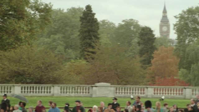 vidéos et rushes de pan from big ben seen thru autumn trees to royal guards riding horses on street / london, england - herbivore