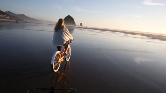 pov from bike following woman biking across wet sand into setting sun - oregonkusten bildbanksvideor och videomaterial från bakom kulisserna