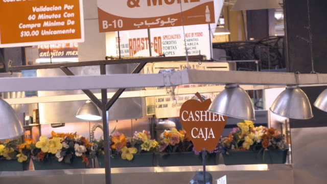 MS ZO from bilingual signage English and Spanish language above food stands selling fresh fruit and vegetables in historic Grand Central Market downtown Los Angeles /Los Angeles, California, USA