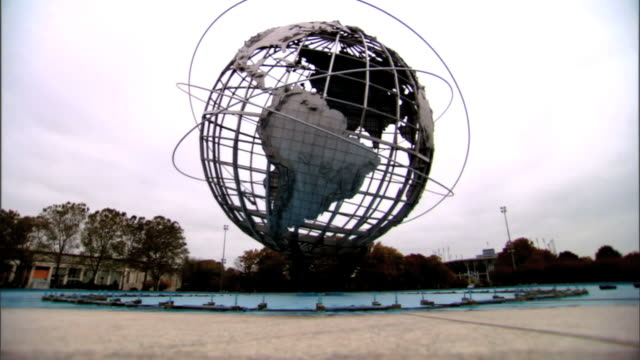 vídeos de stock, filmes e b-roll de from black to ws steel unisphere globe sculpture against white sky on blue fountain granite ledge fg orange green trees two distant buildings bg... - flushing meadows corona park