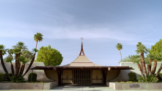 WS TD from blue sky to front entrance of mid-century modern catholic church building