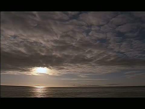 ts, pov from boat travelling over water with sunset glowing with a white light shining through textured clouds blanketing the sky and the light reflecting off the water pan right, silhouette, ms large single hill of land surrounded by water and clouds sca - travelling light stock videos & royalty-free footage