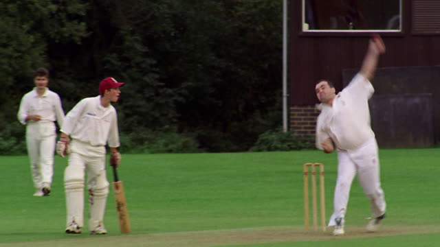 PAN from bowler pitching ball to batsman + wicketkeeper in game of cricket / Hertfordshire, England