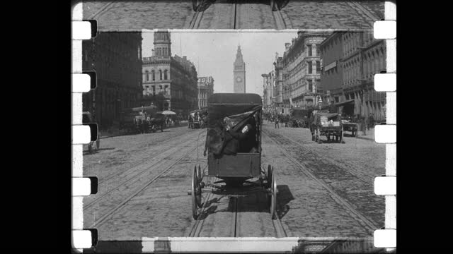 vídeos de stock e filmes b-roll de from cable car traveling east on market street toward the san francisco ferry building, in back of horse drawn cart young boy pokes his head out from... - carroça puxada por cavalo