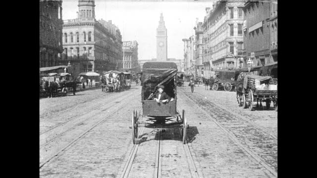 POV from cable car traveling east on Market Street toward the San Francisco Ferry Building / in back of horsedrawn cart young boy pokes his head out...