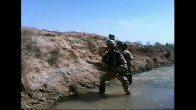 from camera on camera man stuart webb's helmet - showing coldstream guards coming under taliban gunfire as wading along bed of stream - reporter seen... - sergeant stock videos & royalty-free footage