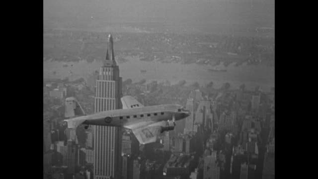 stockvideo's en b-roll-footage met airplane flies past the empire state building passes over manhattan and new york harbor / note exact year not known documentation incomplete - empire state building