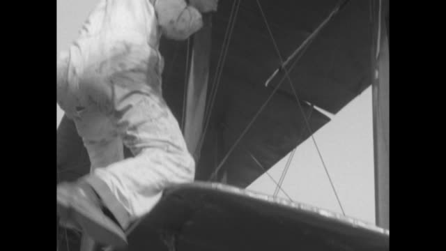 vídeos de stock, filmes e b-roll de from camera plane of two cars driving on road with biplane flying above / stuntman stands on top of moving car, motions to plane pilot to get closer... - gravata borboleta