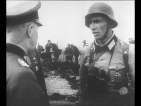 from captured german film: montage german officer speaks with german soldiers as others examine abandoned equipment in background; materiel was left... - other stock videos & royalty-free footage