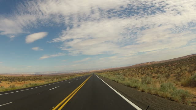POV from car as it drives along desert road
