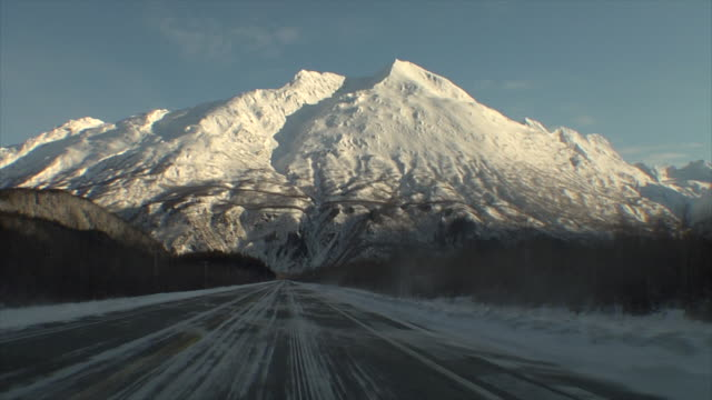 POV from car driving on icy road towards mountain in winter