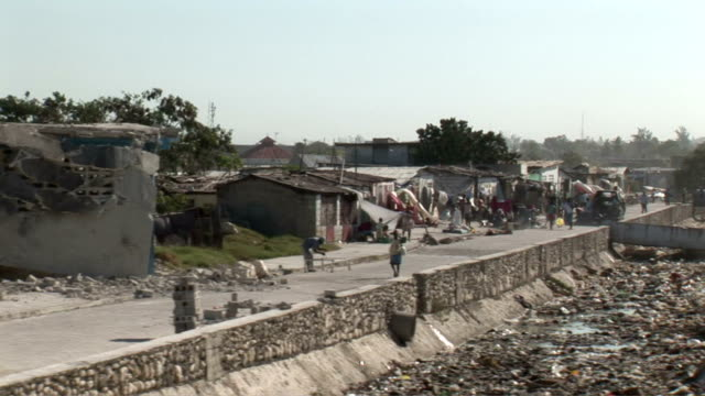 from car of damaged buildings and rubble after haiti earthquake / displaced people / people walking on crowded streets. haiti streets after... - port au prince stock videos & royalty-free footage