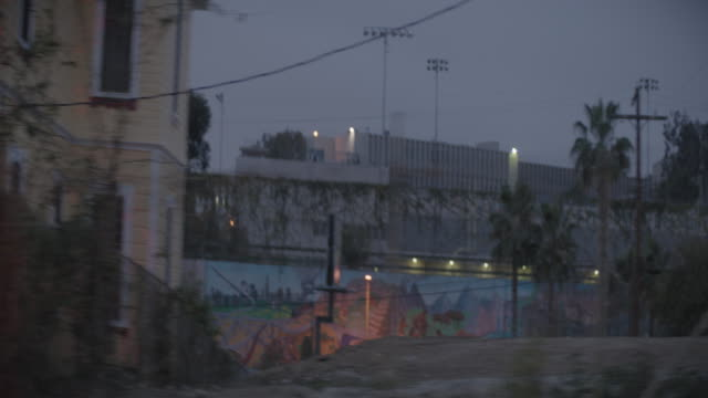 pov from car of houses and graffiti covered wall at dawn, los angeles, ca, usa - twilight stock videos & royalty-free footage