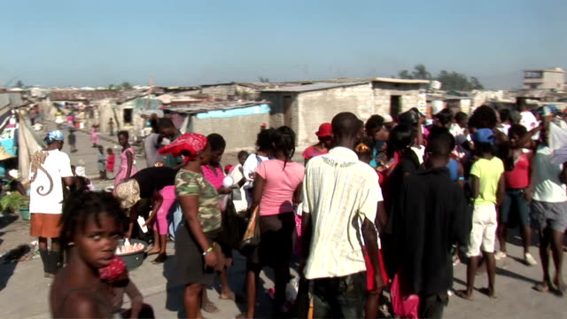 pov from car of refugee camps after earthquake / people in long lines on city streets earthquake refugee camps in haiti on january 13 2010 in... - ポルトープランス点の映像素材/bロール