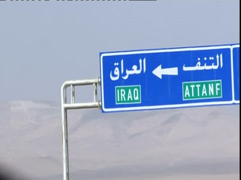 POV from car passenger looking toward sign for Iraq, Syria (sound available)