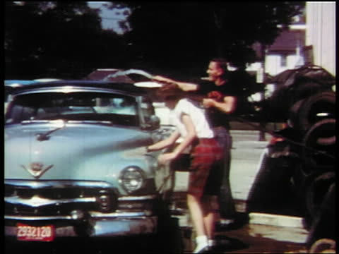 "vídeos y material grabado en eventos de stock de 1957 pan from ""car wash"" sign to teens washing cars outdoors / educational - 1957"