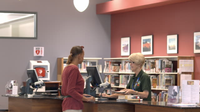 ms td from check out sign to check out counter at public library as employee scans dvd and books while woman customer waits / rancho mirage, california, usa - 公共図書館点の映像素材/bロール