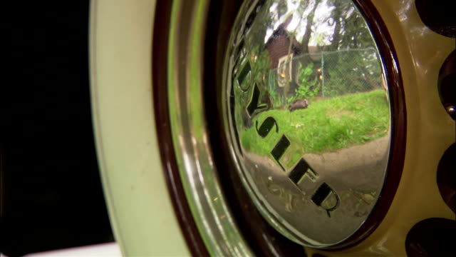 stockvideo's en b-roll-footage met from 'chrysler' sign on silver hubcap of 1934 chrysler airflow parked on street pre 1934 era cars vehicle automobile first streamliner air flow car... - chrysler