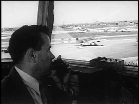 b/w 1951 pan from close up man talking on radio in control tower to airliner taxiing on runway outdoors - vehicle interior stock videos & royalty-free footage